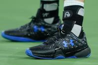 The shoes of Andy Murray, of Britain, is seen with his wedding ring tied to them as he plays Adrian Mannarino, of France, at the BNP Paribas Open tennis tournament Friday Oct. 8, 2021, in Indian Wells, Calif. (AP Photo/Mark J. Terrill)