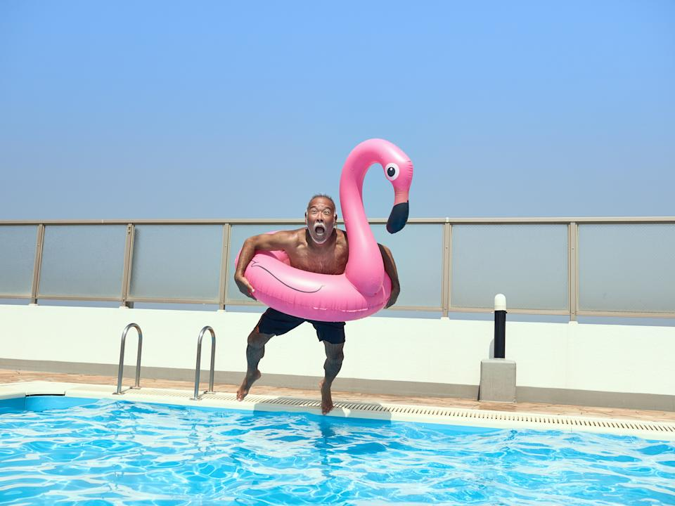 Senior man jumping into the pool with a pink swan-shaped float.