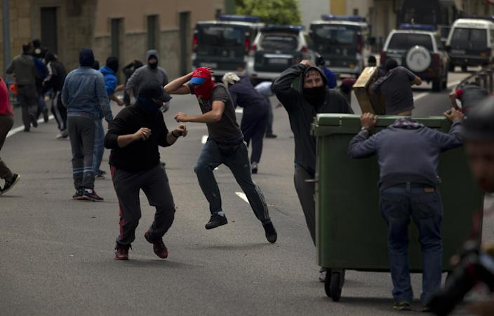 Coal miners run away from police officers during clashes inside a village after blocking a road in Cinera, near Leon, Spain, Tuesday, June 19, 2012. Striking Spanish coal miners firing homemade rockets and using slingshots have clashed with authorities in northern Spain, driving officers out a town where the miners cut off a highway and railroad service. (AP Photo/Emilio Morenatti)
