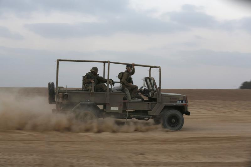 Israeli soldiers ride a military vehicle outside the northern Gaza Strip