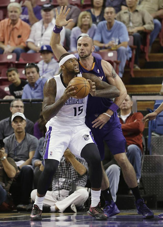 Sacramento KIngs center DeMarcus Cousins, left, goes to the basket against Phoenix Suns center Marcin Gortat, of Poland, during the first quarter of an NBA preseason basketball game in Sacramento, Calif., Thursday, Oct. 17, 2013. (AP Photo/Rich Pedroncelli)