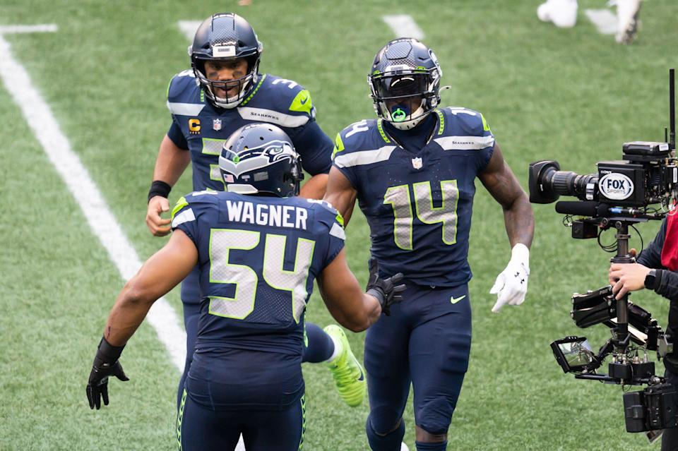Seahawks LB Bobby Wagner congratulates WR DK Metcalf (14) and QB Russell Wilson (3) during last season's playoff game.