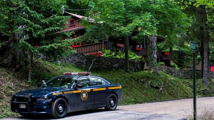 Police outside the home where the suspect, Roy Den Hollander, was found dead