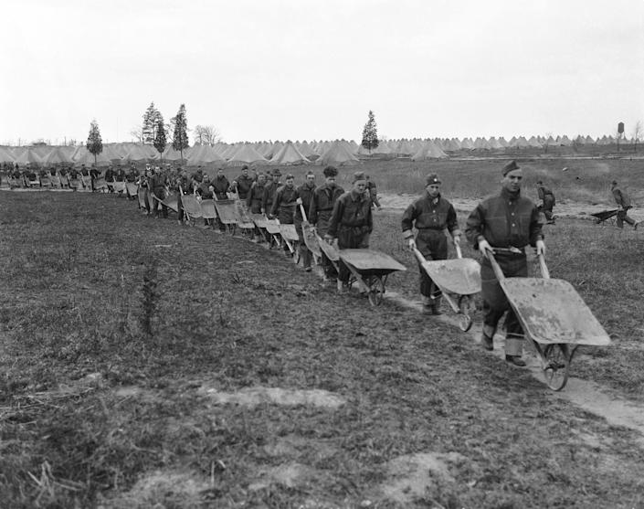A wheel barrow brigade is shown, with men of the Civilian Conservation Corps on their way to building new road at Camp Dix, N.J., date unknown.