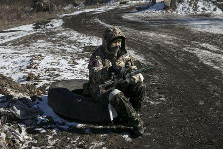 A fighter with the separatist self-proclaimed Donetsk People's Republic Army sits at a checkpoint along a road from the town of Vuhlehirsk to Debaltseve in Ukraine, in this picture taken February 18, 2015. REUTERS/Baz Ratner