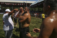 An 'oiler', someone charged with oiling up wrestlers and filling up oil pitchers, douses wrestlers in olive oil, during the 660th instalment of the annual Historic Kirkpinar Oil Wrestling championship, in Edirne, northwestern Turkey, Saturday, July 10, 2021.Thousands of Turkish wrestling fans flocked to the country's Greek border province to watch the championship of the sport that dates to the 14th century, after last year's contest was cancelled due to the coronavirus pandemic. The festival, one of the world's oldest wrestling events, was listed as an intangible cultural heritage event by UNESCO in 2010. (AP Photo/Emrah Gurel)