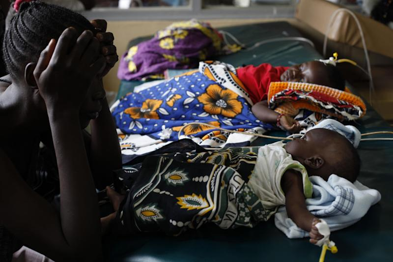 FILE - In this Friday, Oct. 30, 2009 file photo showing an unidetified mother as watches over her child who is suffering from severe malaria, as other children lay nearby, in the Siaya hospital in Western Kenya. Malaria is spread by mosquitoes and kills more than 650,000 people every year, mostly young children and pregnant women in Africa. GlaxoSmithKline and the PATH Malaria Vaccine Initiative, helped develop a new experimental malaria vaccine which was thought promising but is now turning out to be a disappointment, with a new study showing it is only about 30 percent effective at protecting infants from the killer disease according to results released in South Africa Friday Nov. 9, 2012. (AP Photo/Karel Prinsloo, file)