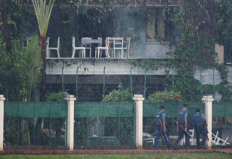 Policemen check the back garden of an upscale cafe in Dhaka on July 3, 2016 a day after a bloody siege ended with the death of 22 hostages, including 18 foreigners