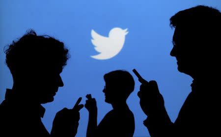 FILE PHOTO - People holding mobile phones are silhouetted against a backdrop projected with the Twitter logo
