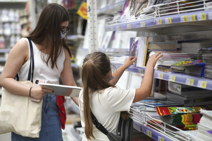 Little girl and her older sister student in a protective medical masks chooses school stationery in a store. Preparing for school. Prevention of coronavirus. Back to school shopping.