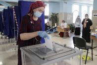 A woman, wearing a face mask to protect against coronavirus casts her ballot, observes social distancing guidelines, at a polling station in Grozny, Russia, Wednesday, July 1, 2020. Russia's vote on constitutional amendments that could allow President Vladimir Putin to extend his rule until 2036 entered its final day Wednesday amid widespread reports of pressure on voters and other irregularities. (AP Photo/Musa Sadulayev)