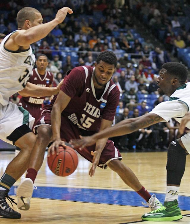 Texas Southern forward D'Angelo Scott (15) drives between Cal Poly forward Chris Eversley (33) and guard Dave Nwaba in the first half of a first-round game of the NCAA college basketball tournament on Wednesday, March 19, 2014, in Dayton, Ohio. (AP Photo/Skip Peterson)