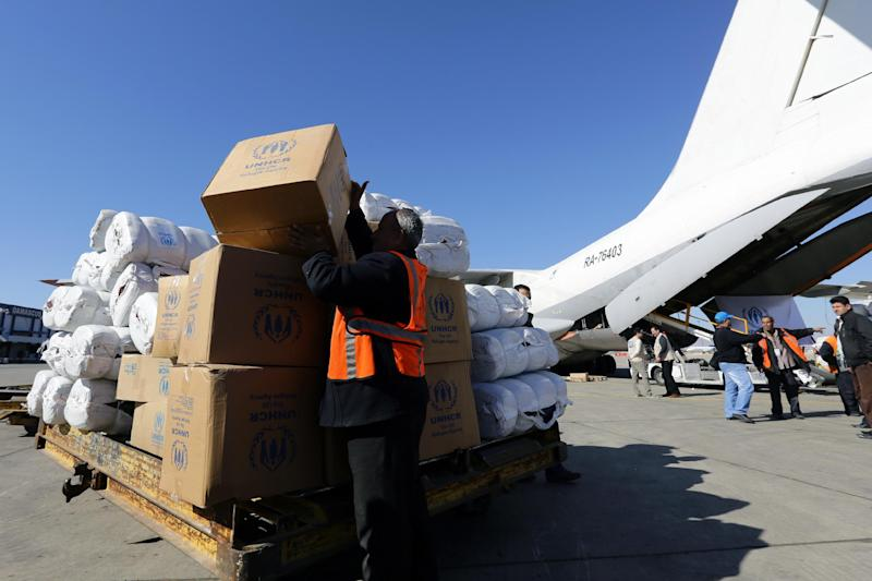 Workers unload from a cargo aircraft, parcels of emergency relief provided by the United Nation's Refugee Agency on February 13, 2014 at Damascus' International Airport (AFP Photo/Louai Beshara)