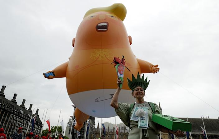 A woman posing as statue of liberty stands next to the 'Trump Baby' blimp as people gather to demonstrate against the state visit of President Donald Trump in Parliament Square, central London, Tuesday, June 4, 2019. Trump will turn from pageantry to policy Tuesday as he joins British Prime Minister Theresa May for a day of talks likely to highlight fresh uncertainty in the allies' storied relationship. (AP Photo/Matt Dunham)