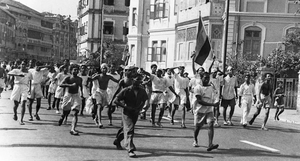 Men of the Royal Indian Navy stream through the streets in Bombay after burning a UK flag during anti-British demonstrations, on February 25, 1946. The flag carried in the foreground is that of the Congress party. The smaller flag near centre is the Muslim League flag. (AP Photo)