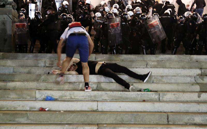 An injured demonstrator receives aid as he lies on the stairs of the Serbian parliament building,during a protest against a lockdown planned for Belgrade this weekend to halt a sruge in coronavirus. - MARKO DJURICA/REUTERS