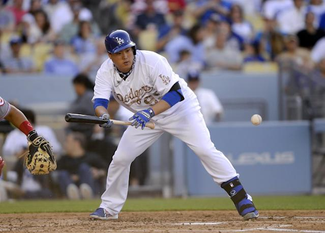 Los Angeles Dodgers starting pitcher Hyun-Jin Ryu hits a sacrifice bunt in the third inning of a baseball game against the Cincinnati Reds, Monday, May 26, 2014, in Los Angeles. (AP Photo/Gus Ruelas)