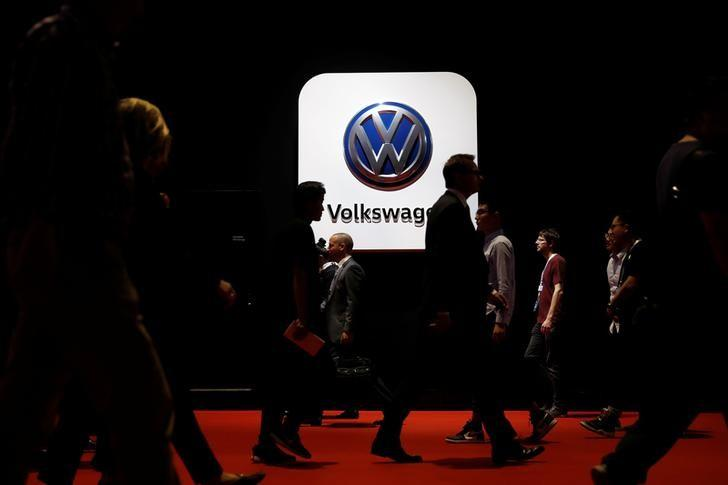 People pass in front of a Volkswagen logo at Shanghai Auto Show during its media day, in Shanghai