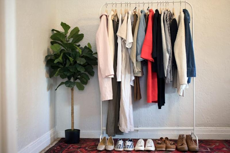 A rack of clothing stands in a person's room.