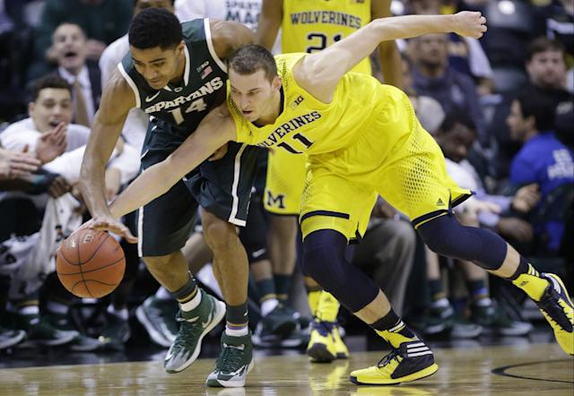 Michigan State guard Gary Harris (14) and Michigan guard Nik Stauskas (11) battle for a loose ball in the first half of an NCAA college basketball game in the championship of the Big Ten Conference tournament on Sunday, March 16, 2014, in Indianapolis. (AP Photo/Michael Conroy)