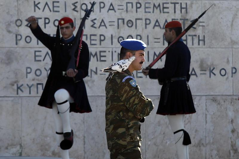 A pigeon sits on the shoulder of a Greek Presidential Guard as his colleagues in traditional Evzones' costumes perform ceremonial duties at the tomb of the unknown soldier in Athens, Wednesday, Oct. 31 2012. Greece's two main labor unions covering civil servants and the private sector have called a 48-hour strike to protest austerity measures due to be voted on next week. The strike call came as the finance minister submitted an amended 2013 budget that raised the country's debt and deficit forecasts for next year. (AP Photo/Kostas Tsironis)