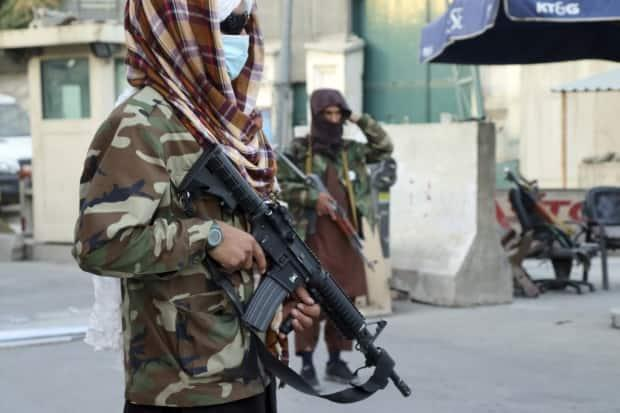 Taliban fighters stand guard at a checkpoint in Kabul on Wednesday. (Khwaja Tawfiq Sediqi/The Associated Press - image credit)