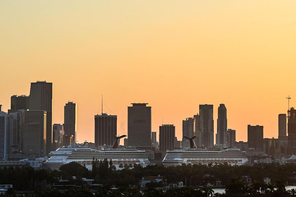 Docked cruise ships are seen at PortMiami in Miami at sunset on April 14, 2021. Cruise ships have been unable to sail in U.S. waters for more than a year.