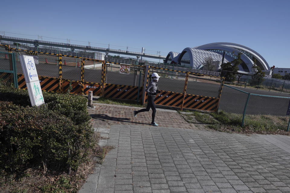 A woman runs near Tokyo Tatsumi International Swimming Center, one of the venues of Tokyo 2020 Olympic and Paralympic games, in Tokyo Wednesday, Jan. 20, 2021. The postponed Tokyo Olympics are to open in just six months. Local organizers and the International Olympic Committee say they will go ahead on July 23. But it's still unclear how this will happen with virus cases surging in Tokyo and elsewhere around the globe. (AP Photo/Eugene Hoshiko)