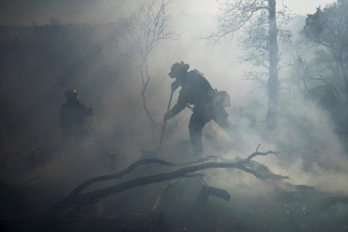 A firefighter extinguishes hotspots while battling the Olinda Fire in Anderson, Calif., Sunday, Oct. 25, 2020. (AP Photo/Noah Berger)