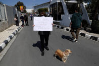 """A protestor walks with her dog, holding a banner reading in Greek """"The satanist does not represent us"""" , outside Cyprus' national broadcasting building, during a protest, in capital Nicosia, Cyprus, Saturday, March 6, 2021. The Orthodox Church of Cyprus is calling for the withdrawal of the country's controversial entry into this year's Eurovision song context titled """"El Diablo"""", charging that the song makes an international mockery of country's moral foundations by advocating """"our surrender to the devil and promoting his worship."""" (AP Photo/Petros Karadjias)"""
