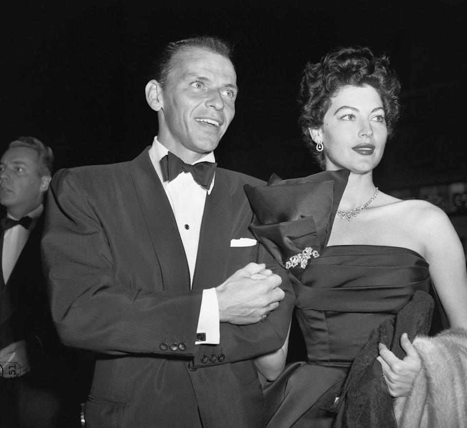 <p>Sinatra and Gardner arrive at an event looking the part of a dapper couple. Gardner wears a dramatic black evening gown and completes the look with diamond jewels and a fur coat. </p>