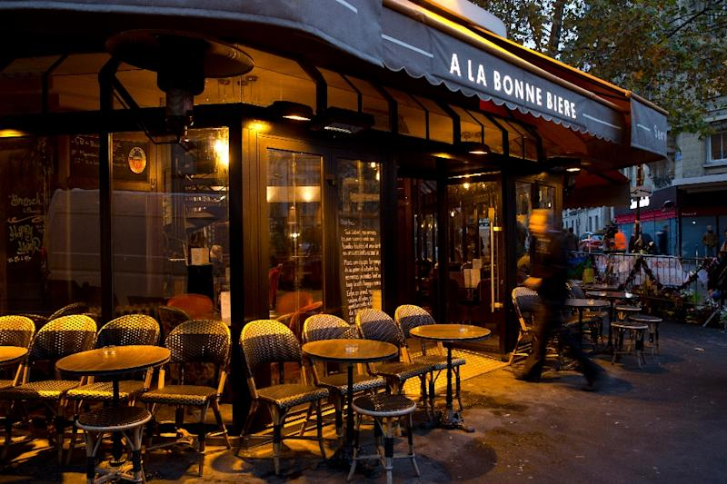 """A man walks past the terrace of the bar """"A la Bonne Biere"""" in Paris on December 4, 2015 The Paris bar where five people were killed by jihadist gunmen in the November 13 attacks is the first of the attacked bars to re-open, in an emotional step in the city's struggle to regain normality. (AFP Photo/Kenzo Tribouillard)"""