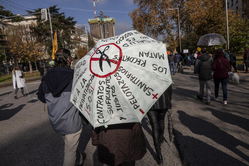 A demonstrator holds an umbrella with messages against the privatisation of the health system during a protest in Madrid, Spain, Sunday, Nov. 29, 2020. The organizers delivered a manifesto to the Madrid regional authorities demanding the end privatization of the health system. (AP Photo/Bernat Armangue)