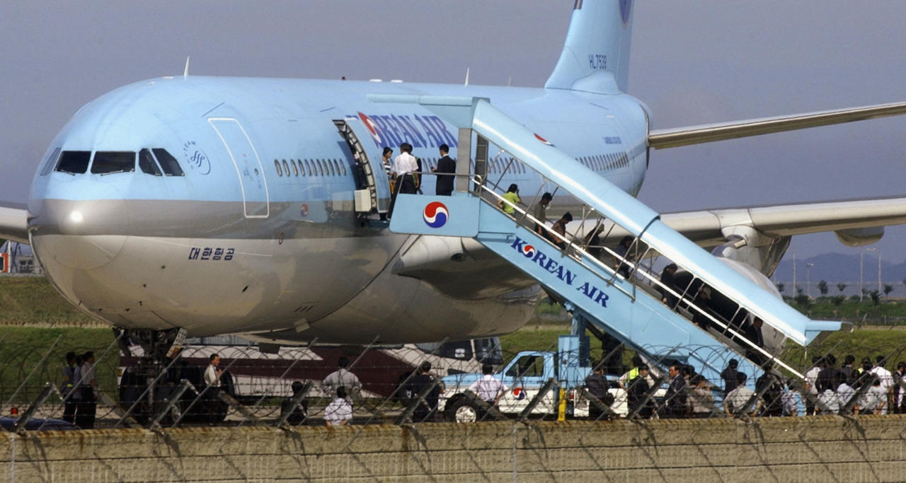 INCHEON, SOUTH KOREA - JULY 28 : North Korean refugees get off an Korean Air plane and move into buses after arriving at Incheon International Airport on July 28 2004 in Incheon, South Korea. More than 200 North Koreans arrived in South Korea today in the second mass influx of defectors from the Stalinist state in two days. It is the largest single group of North Korean defectors to arrive in South Korea for resettlement. (Photo by Kim Dong-Hoon/Getty Images)