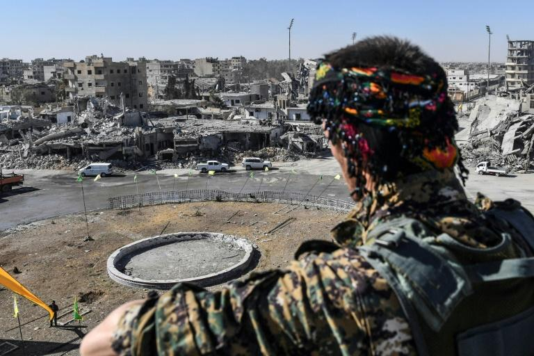 A fighter of the US-backed Syrian Democratic Forces watches over Raqa's Al-Naim square, where the Islamic State group once displayed the severed heads of its enemies, on October 18, 2017, the day after the city's capture