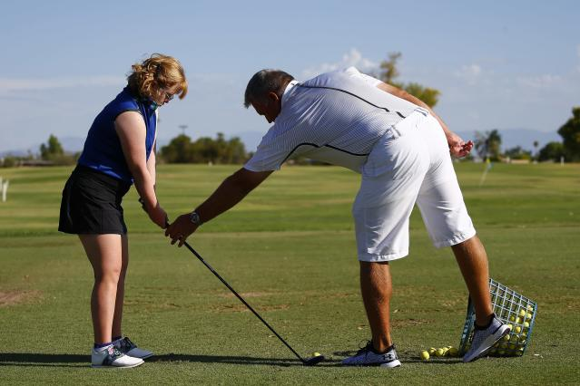 "In this Aug. 28, 2019, photo, Amy Bockerstette, left, practices with her swing coach, Matt Acuff, right, at Palmbrook Country Club in Sun City, Ariz. ""Amy has a huge impact on everyone she meets,"" Acuff said. ""You can't meet Amy and not be impacted by her."" (AP Photo/Ross D. Franklin)"