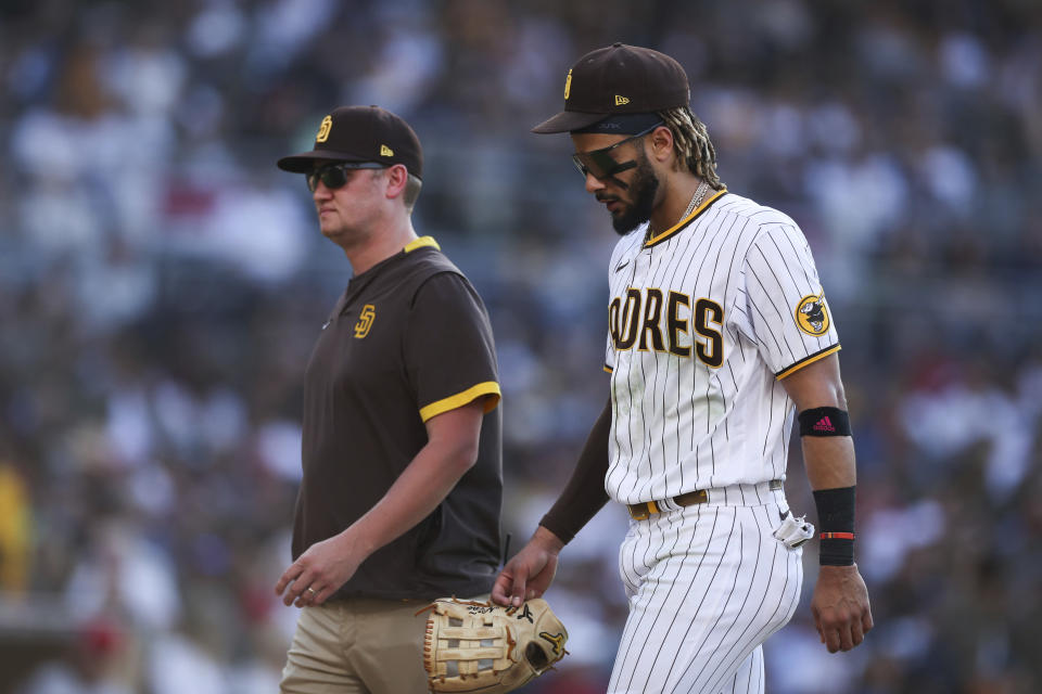 San Diego Padres shortstop Fernando Tatis Jr., right, walks off the field with a trainer in the fifth inning of a baseball game against the Cincinnati Reds, Saturday, June 19, 2021, in San Diego. (AP Photo/Derrick Tuskan)