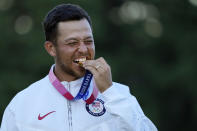 Xander Schauffele, of the United States, walks bites his gold medal in the men's golf at the 2020 Summer Olympics on Sunday, Aug. 1, 2021, in Kawagoe, Japan. (AP Photo/Andy Wong)