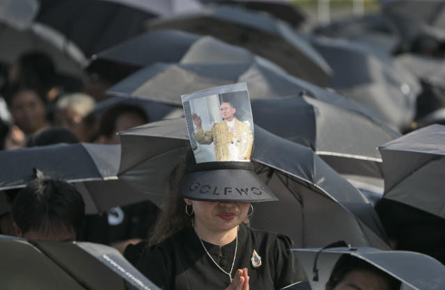 <p>A mourner prays in a sea of black umbrellas at the funeral procession and royal cremation ceremony of late Thai King Bhumibol Adulyadej, seen on photograph, in Bangkok, Thailand, Thursday, Oct. 26, 2017. (Photo: Wason Wanichakorn/AP) </p>