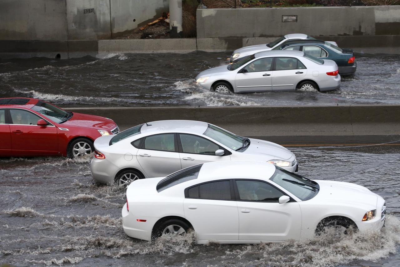 Vehicles drive through a rain-flooded portion of the Interstate 5 freeway in Los Angeles, California March 1, 2014. A torrential rain storm continued to soak California on Saturday forcing some homeowners to evacuate, creating rock and mudslides, and stranding drivers on flooded roads. REUTERS/Jonathan Alcorn (UNITED STATES - Tags: DISASTER ENVIRONMENT TRANSPORT)