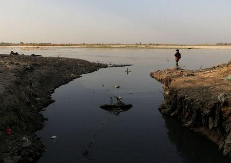 A boy stands next to an open drain on the banks of river Ganges in Kanpur, India, April 3, 2017. REUTERS/Danish Siddiqui