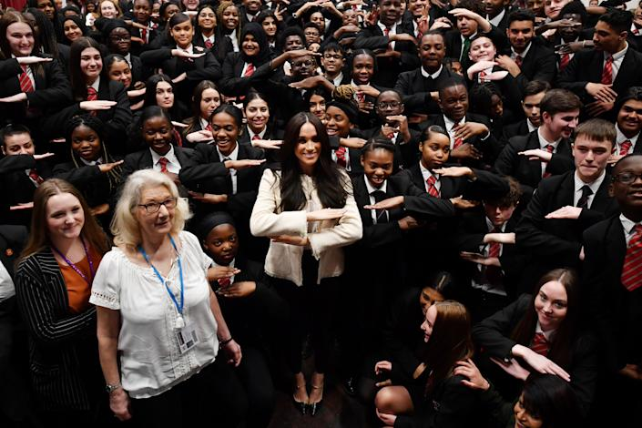 Meghan joined the schoolchildren in making the each for equal hand sign. (Getty Images)