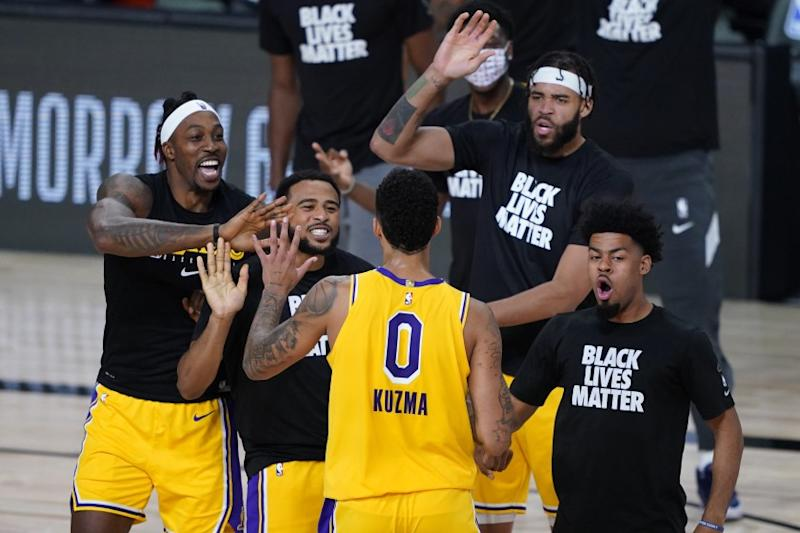 Los Angeles Lakers' Kyle Kuzma (0) is congratulated by teammates after hitting a game-winning 3-pointer.