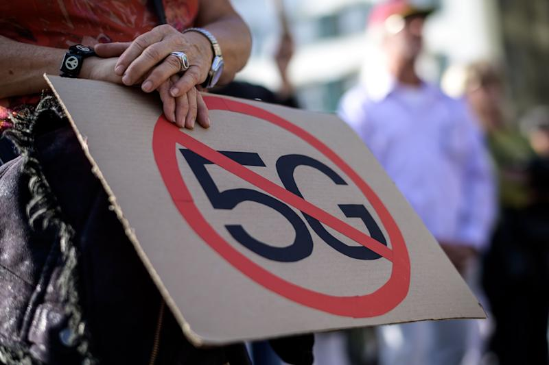 TOPSHOT - People take part in a national demonstration against 5G technology and the deployment of 5G-compatible antennas outside the Swiss Parliament in Bern, on September 21, 2019. - Switzerland was one of the first countries to deploy 5G, but health concerns about the radiation of antennas carrying next-generation mobile technology have triggered a nationwide revolt. (Photo by Fabrice COFFRINI / AFP) (Photo credit should read FABRICE COFFRINI/AFP/Getty Images)