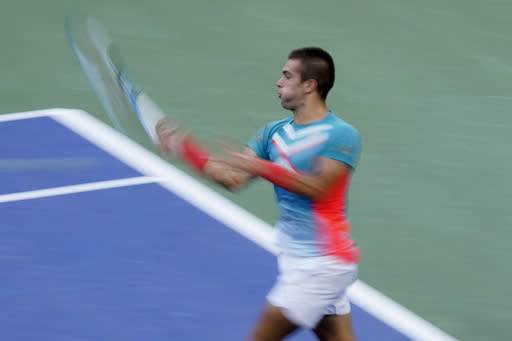 In this photo taken with a slow shutter speed, Borna Coric, of Croatia, returns a shot to Jordan Thompson, of Australia, during the fourth round of the US Open tennis championships, Sunday, Sept. 6, 2020, in New York. (AP Photo/Frank Franklin II)
