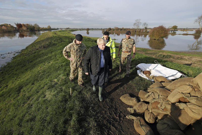 Britain's Prime Minister Boris Johnson, foreground, walks with Lt Col Tom Robinson, left,  from the Light Dragoons and an Environment Agency official  during a visit to see the effects of recent flooding, in Stainforth, England, Wednesday, Nov. 13, 2019. (Danny Lawson/Pool Photo via AP)