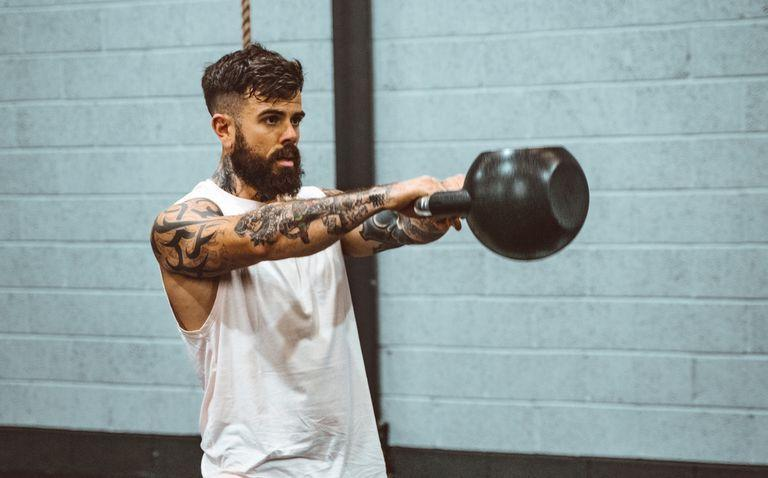 """<p><strong>You'll need: </strong><strong>2 x Dumbbells, </strong><strong>pull-up bar, </strong><strong>floor space</strong></p><p>We've adapted the original workout to make it much more accessible, whether you're back in the gym or training at home. <a href=""""https://www.instagram.com/scottbrits/"""" rel=""""nofollow noopener"""" target=""""_blank"""" data-ylk=""""slk:Scott Britton"""" class=""""link rapid-noclick-resp"""">Scott Britton</a>, co-founder of functional fitness charity movement <a href=""""https://www.instagram.com/battle.cancer/"""" rel=""""nofollow noopener"""" target=""""_blank"""" data-ylk=""""slk:Battle Cancer"""" class=""""link rapid-noclick-resp"""">Battle Cancer</a>, has swapped the barbell for dumbbells and traded the highly technical gymnastics for a classic bodyweight movement. Your aim is to do all 90 reps as quickly as you can. Then rest of the same time as it took you, before repeating for a second round. Then have yourself a lie down.</p><p>2 rounds of: </p><p><strong>1) Dumbbell Clean and Jerk x 30<br></strong>Start with the dumbbells just outside your feet and hinge at the hips to grab them. Stand back up with a slight jump, using the momentum to pull the dumbbells on to your shoulders. Stand up straight. From here dip at the knees, then use power from your legs to help press both of your dumbbells high overhead to lockout. Lower the weights under control to the floor and repeat.</p><p><strong>2)</strong> <strong>Pull-Up x 30</strong><br><br>Grasp a pull-up bar with an overhand grip over shoulder-width apart, lift your feet from the floor, hanging freely with straight arms. Pull yourself up by flexing the elbows whilst pinching your shoulder blades together. When your chin passes the bar, pause before lowering to the starting position.</p><p><strong>3) Dumbbell Snatch x 30</strong></p><p>Begin with one dumbbell on the ground between your legs. Squat down and grab the weight. Drive up through your hips, generating momentum to pull the dumbbell towards the ceiling in one motion, finishing overhe"""