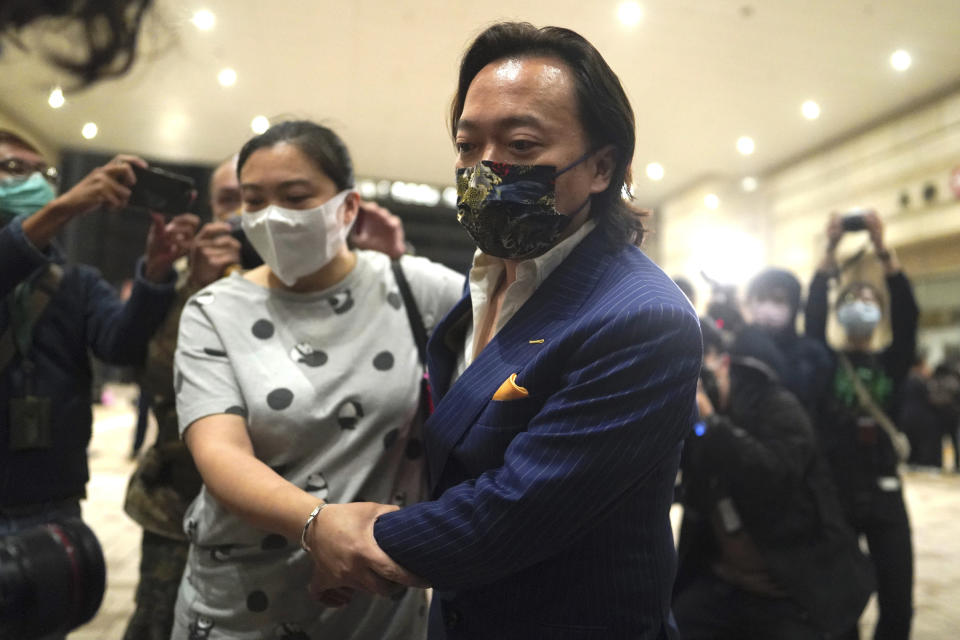 Lawrence Lau, charged with conspiracy, and his relative leave after being released on bail at a court in Hong Kong, Friday, March 5, 2021. Four of the 47 pro-democracy activists charged with conspiracy to commit subversion, including Lau, were released on bail Friday after prosecutors dropped an appeal against the court's decision to grant them bail. (AP Photo/Kin Cheung)