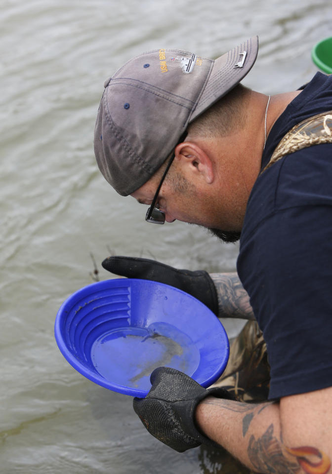 In this photo taken Tuesday, March 4, 2014 Tim Amavisca, 38, pans for gold along the Bear River near Colfax, Calif. Amavisca is among the amateur prospectors that have flocked to the Sierra Nevada foothills that, due to the historic drought, are taking advantage of the lower water levels to search for gold in riverbeds that have been unreachable for decades.(AP Photo/Rich Pedroncelli)