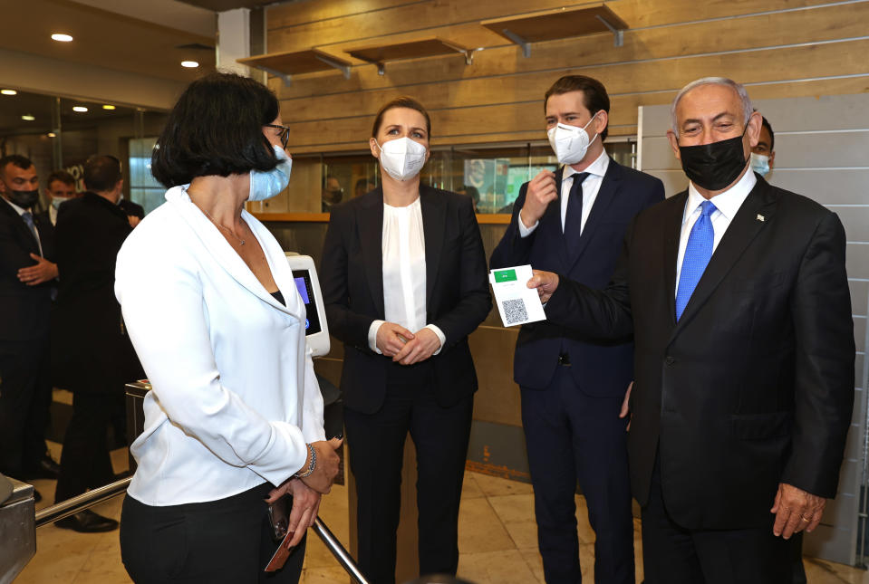 """FILE - In this March 4, 2021, file photo, Israeli Prime Minister Benjamin Netanyahu, right, holds a """"Green Pass,"""" for citizens vaccinated against COVID-19, as he visits a fitness gym with Austrian Chancellor Sebastian Kurz, second right, and Danish Prime Minister Mette Frederiksen, left, to observe how the pass is used, in Modi'in, Israel. While the country's """"green pass"""" system has been successful in the areas of leisure and entertainment, it has proved to be more complicated in the workplace, where stakes are higher. (Avigail Uzi/Pool via AP, File)"""